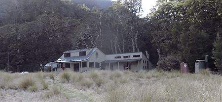 The hut is on the edge of the forest, in the tussock. | Iris Burn Hut, Kepler Track