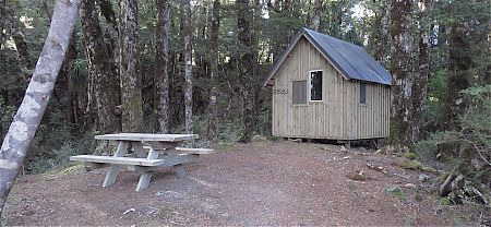 There's two uninsulated shelters, without adequate insect screening, in the forest. | Lyell Saddle sleepout, Lyell Range/Radiant Range Conservation Area