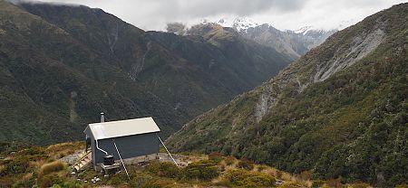 The hut is perched near the edge of a bluff. | Bluff Hut, Hokitika River, West Coast