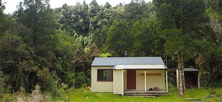 Frew is up on a river terrace with some young kahikateas around. | Frew Hut, Whitcomb River, West Coast