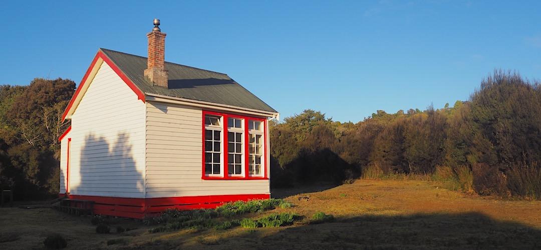 Yup. Looks like an old schoolhouse with a vibrant colour scheme.  | Port Craig Schoolhouse Hut, near Fiordland National Park