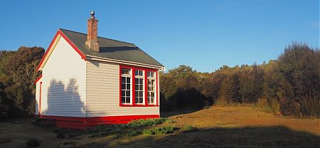 Yup. Looks like an old schoolhouse with a vibrant colour scheme.  | Port Craig Schoolhouse Hut, near Fiordland National Park