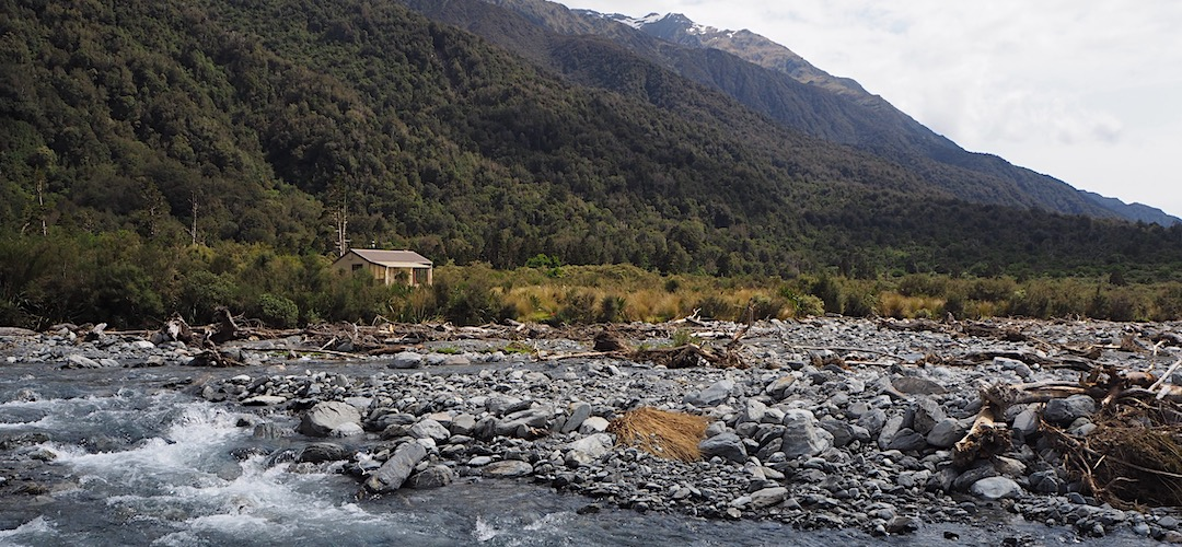 Grassy Flat Hut is located right by one branch of the river. | Grassy Flat Hut, Styx River, West Coast