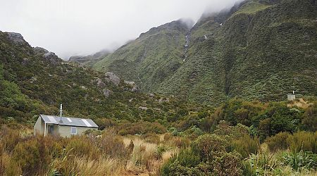 Harman Hut is located on a flat area near a river junction.  | Harman Hut, Arahura River, West Coast
